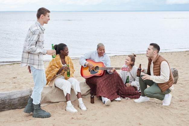 Retrato de corpo inteiro de um grupo diversificado de amigos curtindo acampar na praia no outono e tocando violão