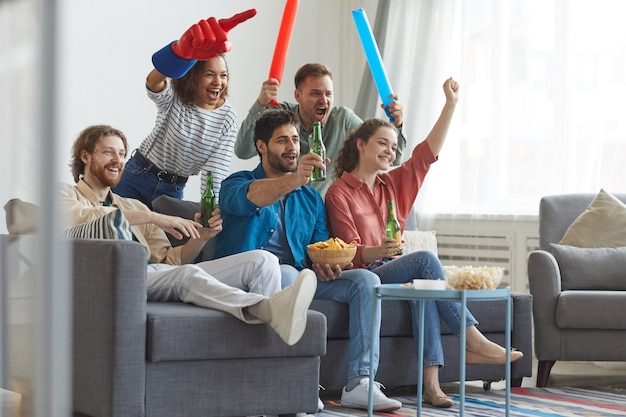Retrato de corpo inteiro de um grupo multiétnico de amigos assistindo a uma partida de esportes na tv e torcendo emocionalmente enquanto estão sentados juntos no sofá