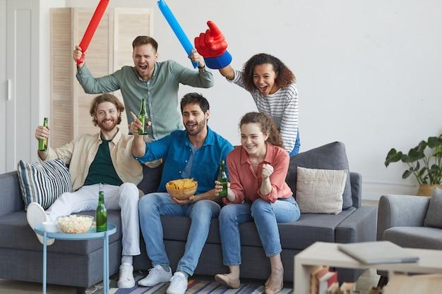 Retrato de corpo inteiro de um grupo multiétnico de amigos assistindo a uma partida de esportes na tv e torcendo emocionalmente, sentados juntos no sofá