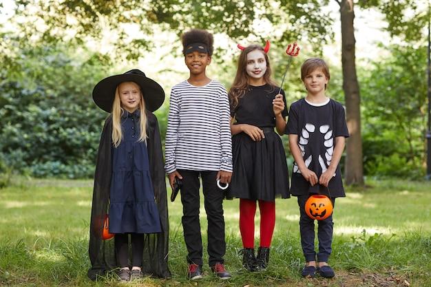 Retrato de corpo inteiro de um grupo multiétnico de crianças vestindo fantasias de halloween ao ar livre e