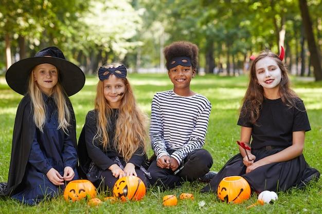 Retrato de corpo inteiro de um grupo multiétnico de crianças vestindo fantasias de halloween e sentadas na grama verde ao ar livre