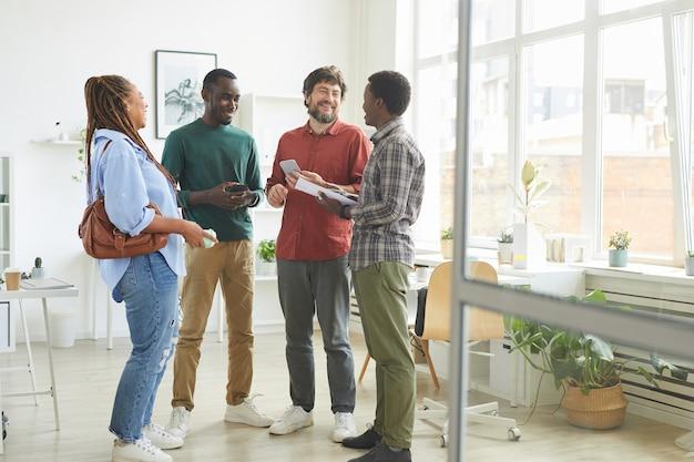 Retrato de corpo inteiro de um grupo multiétnico de pessoas vestidas com roupas casuais e sorrindo alegremente enquanto discutem o trabalho em pé no escritório