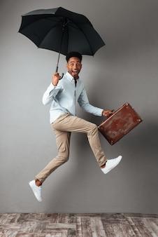 Retrato de corpo inteiro de um homem africano alegre feliz pulando