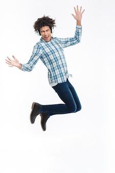 Retrato de corpo inteiro de um homem afro-americano alegre em fones de ouvido, pulando isolado em uma parede branca