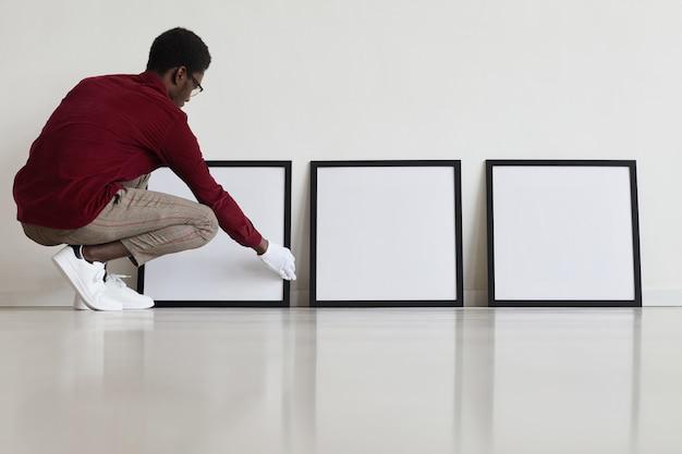 Retrato de corpo inteiro de um homem afro-americano colocando molduras pretas vazias no chão enquanto planeja uma galeria de arte ou exposição.