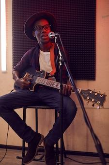 Retrato de corpo inteiro de um homem afro-americano contemporâneo tocando violão