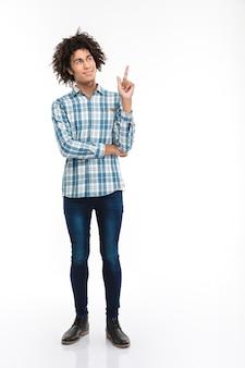 Retrato de corpo inteiro de um homem afro-americano feliz e pensativo, com cabelo encaracolado apontando o dedo para copyspace isolado em uma parede branca