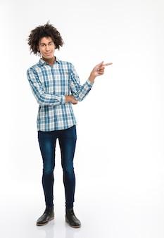 Retrato de corpo inteiro de um homem afro-americano sorridente com cabelo encaracolado apontando o dedo para longe, isolado em uma parede branca