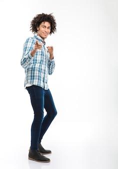 Retrato de corpo inteiro de um homem afro-americano sorridente com cabelo encaracolado, apontando os dedos isolados em uma parede branca