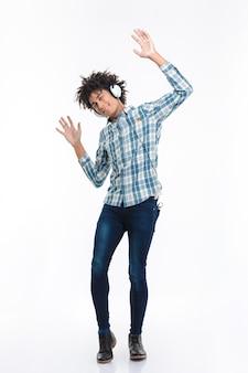 Retrato de corpo inteiro de um homem afro-americano sorridente, ouvindo música em fones de ouvido e dançando isolado em uma parede branca