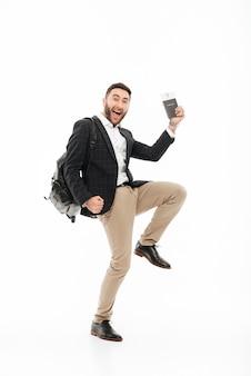 Retrato de corpo inteiro de um homem alegre e animado, segurando o passaporte