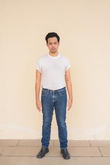Retrato de corpo inteiro de um homem asiático vestindo uma camiseta branca contra um fundo liso ao ar livre