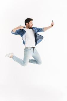 Retrato de corpo inteiro de um homem barbudo bonito animado, vestindo roupas casuais, pulando isolado, tirando uma selfie