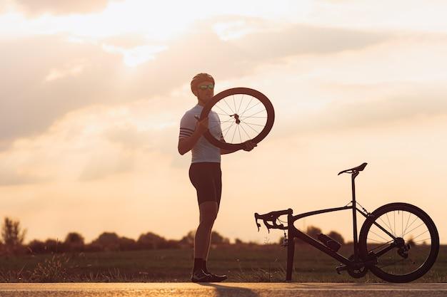 Retrato de corpo inteiro de um homem barbudo bonito em roupa esportiva, capacete e óculos ajustando a roda de bicicleta preta ao ar livre