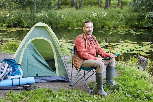Retrato de corpo inteiro de um homem barbudo maduro pescando no lago e sorrindo para a câmera no acampamento, copie o espaço
