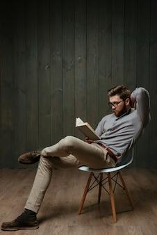Retrato de corpo inteiro de um homem barbudo pensativo lendo um livro enquanto está sentado na cadeira, isolado em uma superfície de madeira preta
