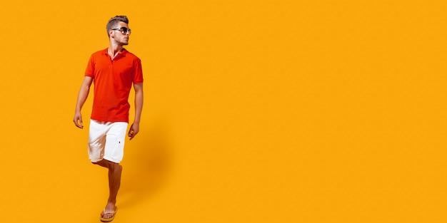 Retrato de corpo inteiro de um homem bonito de bermuda e camisa vermelha andando e olhando de lado, isolado no amarelo