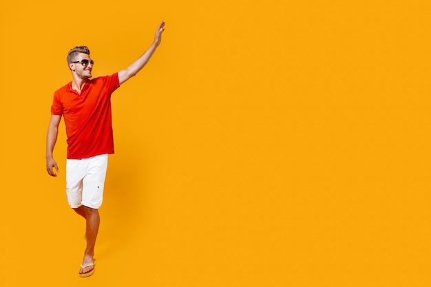 Retrato de corpo inteiro de um homem bonito de bermuda e camisa vermelha andando olhando para o lado ergueu a mão em saudação