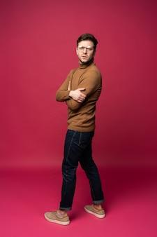 Retrato de corpo inteiro de um homem bonito, de pé com os braços cruzados, isolado em um fundo rosa.