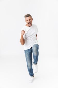 Retrato de corpo inteiro de um homem bonito e casual pulando isolado no branco, celebrando o sucesso