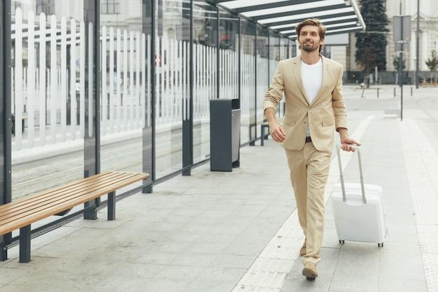 Retrato de corpo inteiro de um homem bonito em um terno moderno andando no ponto de ônibus com uma mala branca