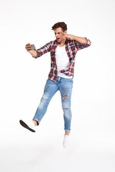 Retrato de corpo inteiro de um homem casual, tomando uma selfie