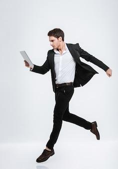 Retrato de corpo inteiro de um homem de negócios jovem concentrado pulando e olhando para um computador tablet isolado em uma parede branca