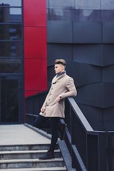 Retrato de corpo inteiro de um homem estiloso com um casaco na cidade