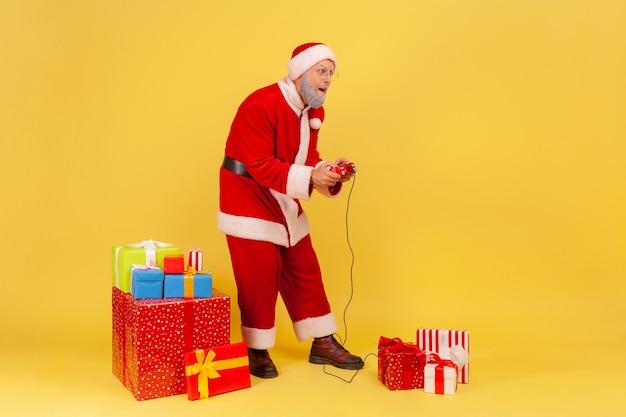 Retrato de corpo inteiro de um homem idoso com barba grisalha, vestindo fantasia de papai noel, jogando videogame na véspera de ano novo com expressão concentrada. estúdio interno, tiro isolado em fundo amarelo.