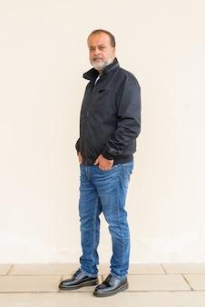 Retrato de corpo inteiro de um homem indiano barbudo bonito contra uma parede simples