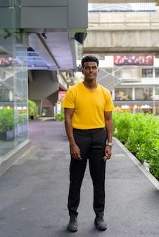 Retrato de corpo inteiro de um homem negro africano bonito vestindo uma camiseta amarela ao ar livre na cidade durante o verão