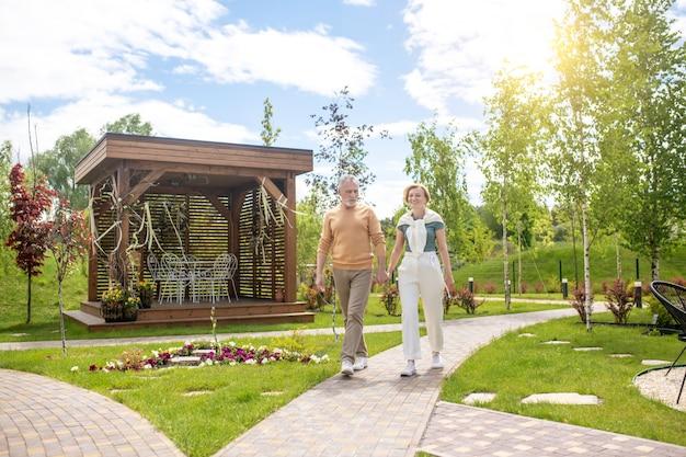 Retrato de corpo inteiro de um homem pensativo e sua mulher alegre caminhando de mãos dadas