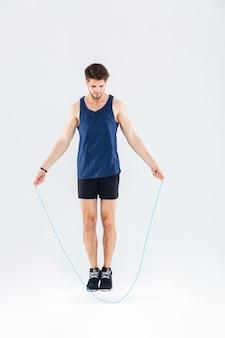 Retrato de corpo inteiro de um homem pulando com pular corda, isolado em um fundo cinza