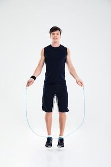 Retrato de corpo inteiro de um homem pulando com pular corda isolado