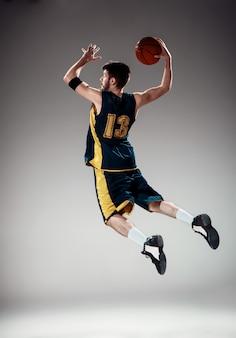 Retrato de corpo inteiro de um jogador de basquete com bola
