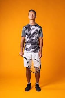 Retrato de corpo inteiro de um jogador de tênis em ação contra um fundo laranja close-up
