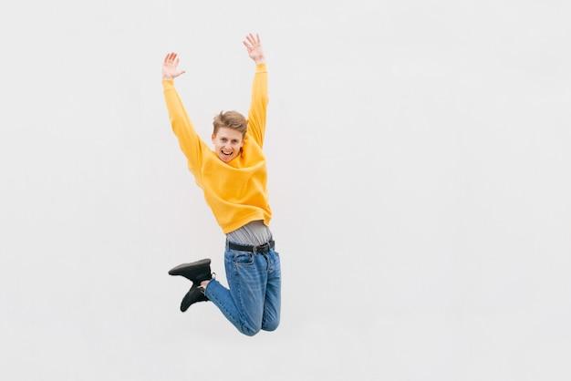 Retrato de corpo inteiro de um jovem alegre em uma camiseta branca apontando os dedos para longe