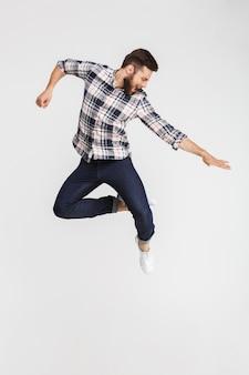 Retrato de corpo inteiro de um jovem alegre pulando