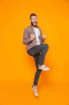 Retrato de corpo inteiro de um jovem alegre, vestindo roupas casuais, comemorando o salto