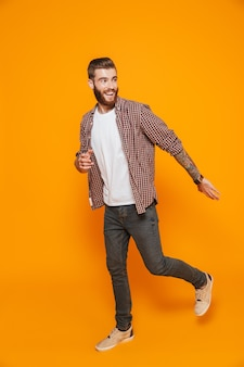 Retrato de corpo inteiro de um jovem alegre, vestindo roupas casuais, indo embora