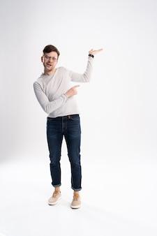Retrato de corpo inteiro de um jovem alegre, vestindo roupas casuais, isoladas sobre fundo branco