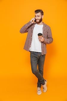 Retrato de corpo inteiro de um jovem alegre, vestindo roupas casuais, segurando uma xícara de café para viagem, falando no celular