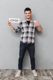 Retrato de corpo inteiro de um jovem animado com placa aberta