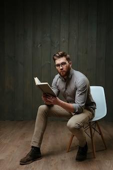 Retrato de corpo inteiro de um jovem barbudo de óculos segurando um livro enquanto está sentado na cadeira e olhando para a frente, isolado em uma superfície de madeira preta