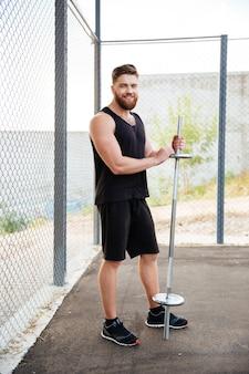 Retrato de corpo inteiro de um jovem bonito e sorridente homem de fitness segurando uma barra ao ar livre