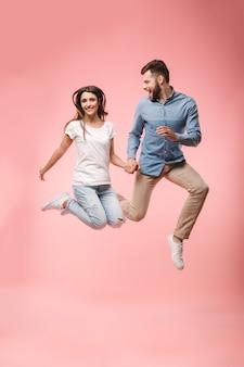 Retrato de corpo inteiro de um jovem casal feliz de mãos dadas