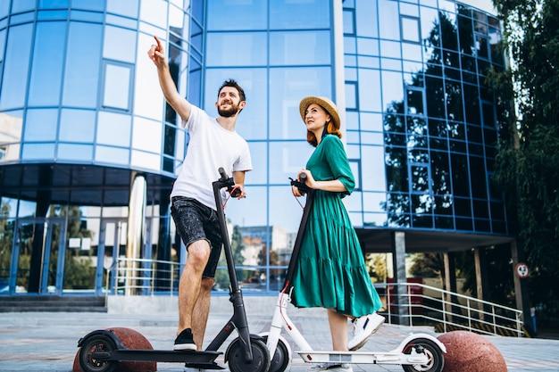 Retrato de corpo inteiro de um jovem casal romântico com scooters elétricos, andando na cidade. jovem de chapéu e homem desfrutar de um passeio