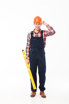 Retrato de corpo inteiro de um jovem construtor masculino bonito