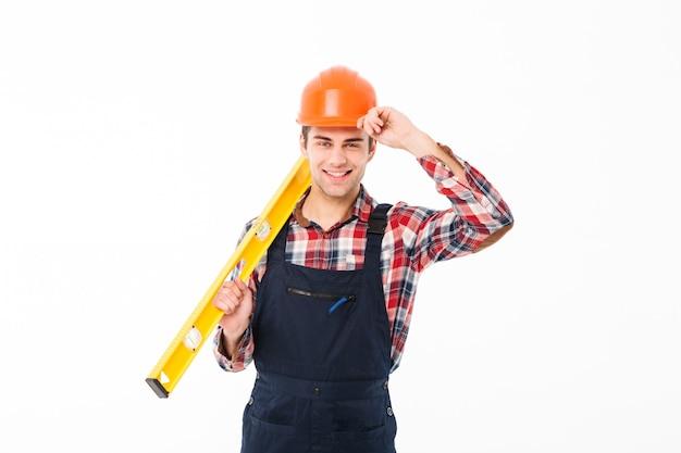 Retrato de corpo inteiro de um jovem construtor masculino feliz