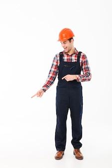 Retrato de corpo inteiro de um jovem construtor masculino sorridente